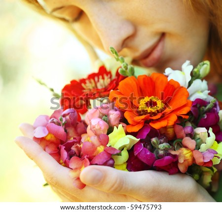 Young woman with flowers over natural background - stock photo