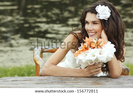 young woman with flowers summer outdoor, beautiful bride has fun in summer park - stock photo