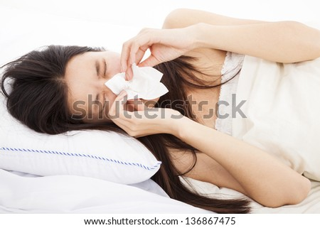 young Woman with flu and laying in bed - stock photo