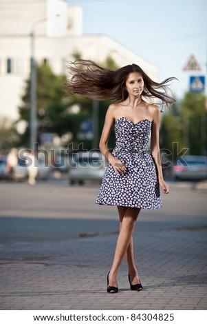 young woman with fluttering hair at the street in city - stock photo