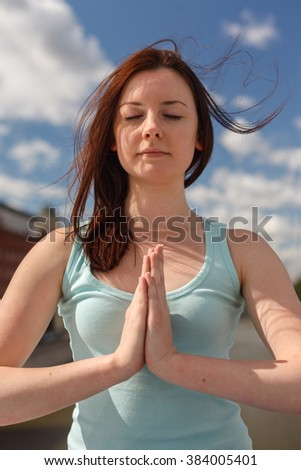 Young woman with flying hair in meditation pose - stock photo