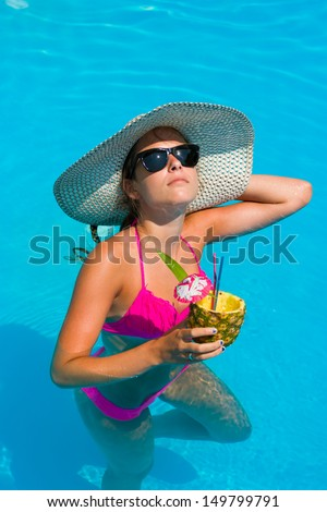 Young woman with fresh cocktail in the swimming pool - stock photo