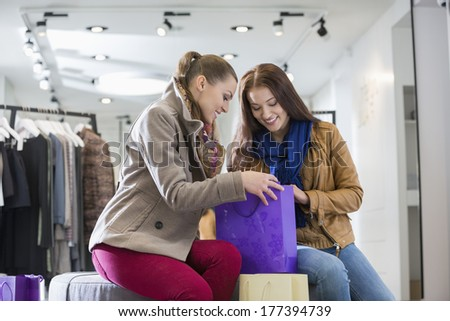 Young woman with friend looking into shopping bag at store - stock photo