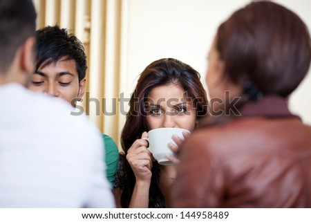 Young woman with friends in a cafe - stock photo