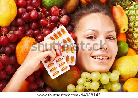 Young woman with fruit and vitamin pill. Isolated. - stock photo