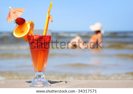 young woman with fruit cocktail relaxing on beach - stock photo