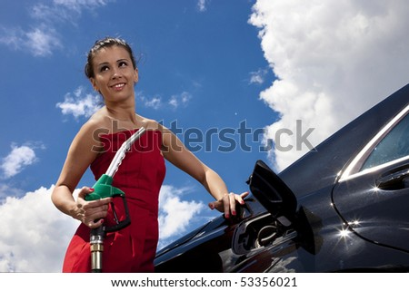 Young woman with fuel nozzle on gas station with black car and sky