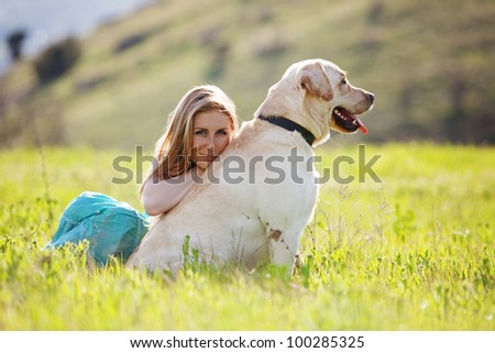 Young woman with ger dog resting at green field - stock photo