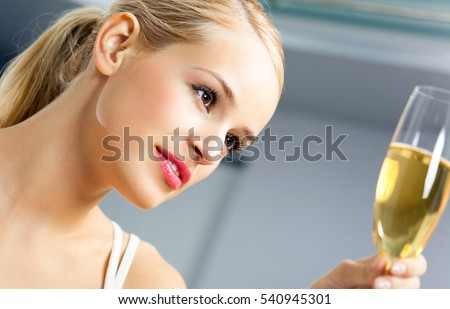 Young woman with glass of champagne, at home
