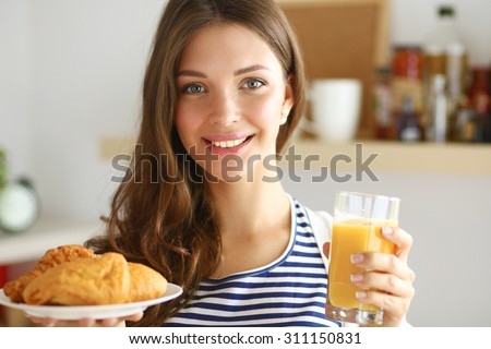 Young woman with glass of juice and cakes - stock photo