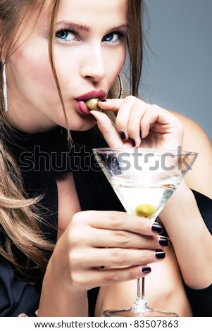 young woman with glass  of martini and olive in mouth, studio shot - stock photo