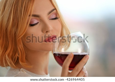 Young woman with glass of red wine on light blurred background