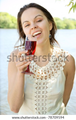 Young woman with glass of wine near river