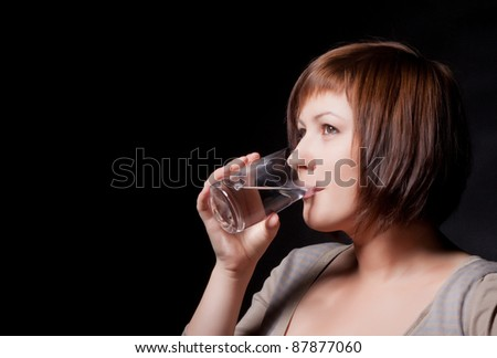 young woman with glass water, black background - stock photo