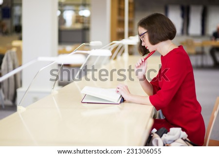 Young woman with glasses in library study text - stock photo