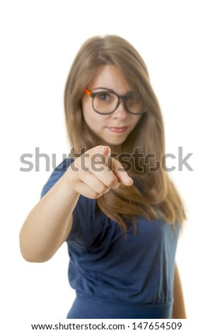 Young woman with glasses point at observer. Focus on finger
