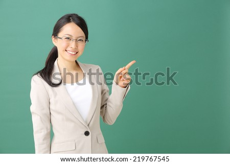 young woman with glasses pointing copy space against blackboard - stock photo