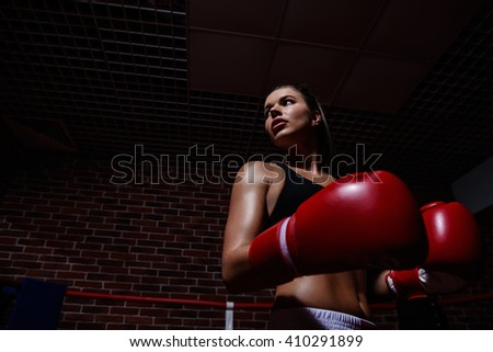 Young woman with gloves in boxing ring - stock photo