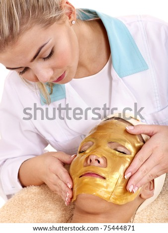 Young woman with gold facial mask. - stock photo