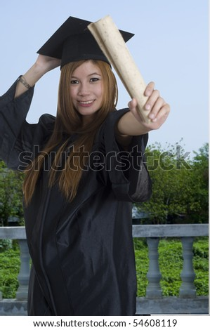 Young woman with graduation cap and gown holding her diploma - stock photo