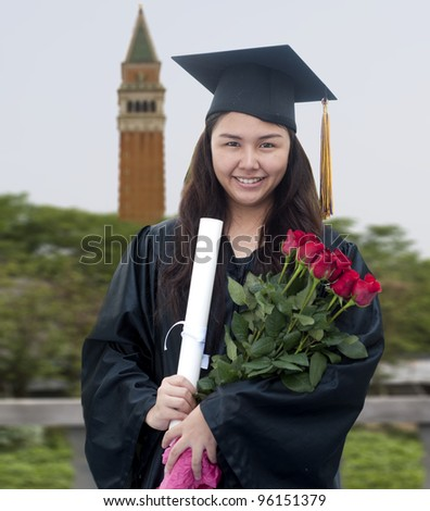 Young woman with graduation cap and gown holding roses