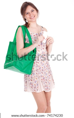 young woman with green ecological shopping bag checking purchases list - stock photo