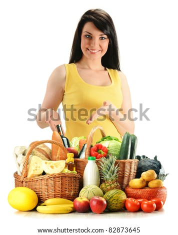 Young woman with groceries in wicker basket isolated on white. Variety of products including vegetables, fruits, dairy, wine and bread
