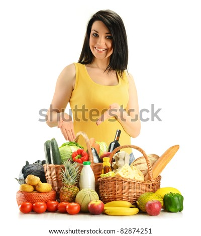 Young woman with groceries in wicker baskets isolated on white. Variety of products including vegetables, fruits, dairy, wine and bread - stock photo