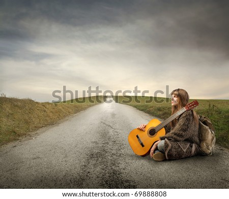 Young woman with guitar and backpack sitting on a countryside road - stock photo