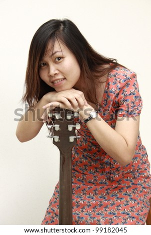 Young woman with guitar on white background - stock photo