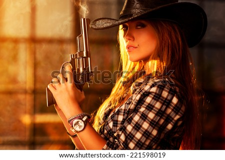 Young woman with gun portrait. - stock photo