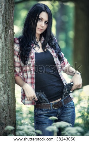 Young woman with guns in a forest.