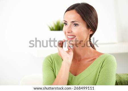 Young woman with hair back smiling and looking away with confidence at indoors - copy space - stock photo
