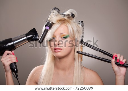 Young woman with hairdryer and hairbrushes in her hair - stock photo