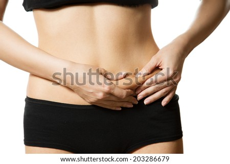 Young woman with hand on her tummy. Part of body. Close-up. Isolated over white background. - stock photo