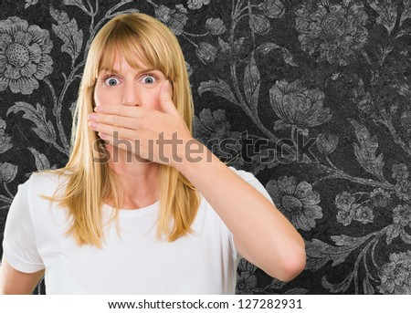 Young Woman With Hand On Mouth against a vintage wall - stock photo