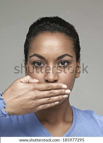 Young woman with hand over mouth - stock photo