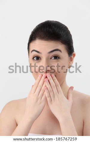 Young woman with hand over mouth, portrait