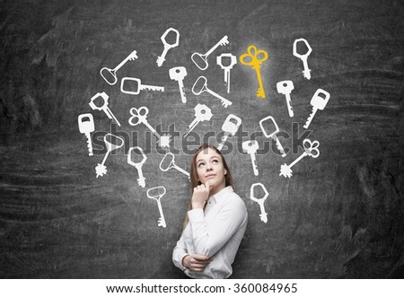 Young woman with hand to the chin looking up in search of the right solution which are presented as keys around her. Black background. Concept of finding a solution. - stock photo