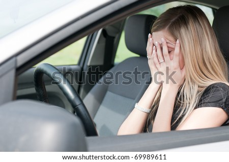 Young woman with hands on eyes sitting depressed in car - stock photo