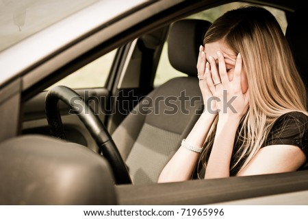 Young woman with hands on eyes sitting depressed in car