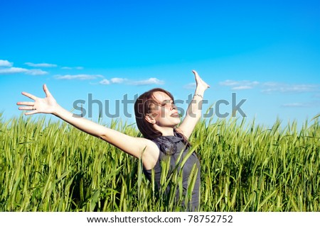 young woman with hands raised up in the wheat field - stock photo