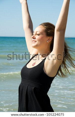 Young woman with hands up expressing joy on the coast
