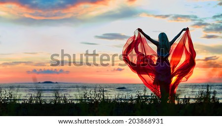Young woman with hands up holding red scarf in wind on the beach - stock photo