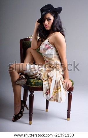 young woman with hat sitting on chair