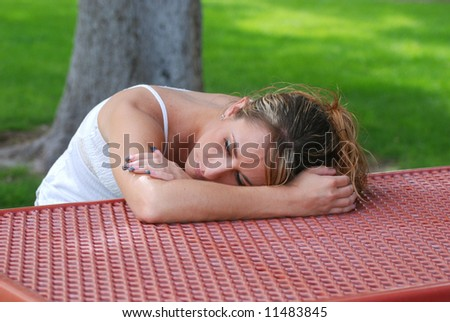 Young woman with head on a park picnic table while she thinks. - stock photo