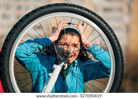 Young woman with headache is trying to fix bike problem - stock photo