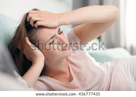 Young woman with headache lying on couch at home, casual style indoor shoot - stock photo