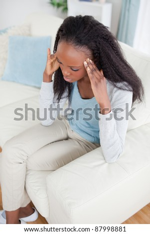 Young woman with headache sitting on sofa