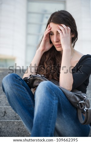 Young woman with headache - sitting outdoor holding head - stock photo